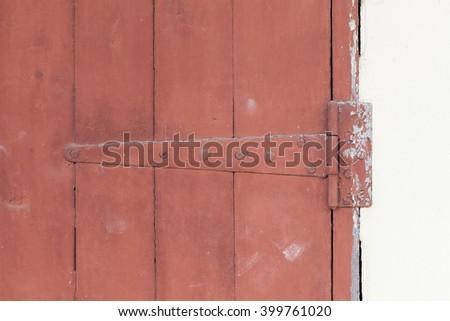 An old door hinge of old wooden door with weathered paint - stock photo