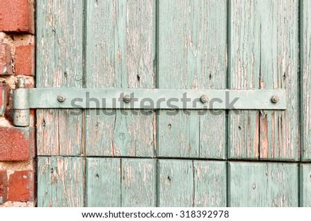 An old door hinge of old wooden door with weathered paint in Zelhem, The Netherlands. - stock photo
