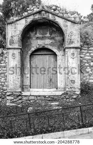 An old door with the stone wall surrounding of an old building, during daylight, located in Plaka, Athens, Greece. - stock photo