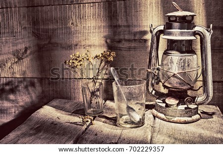 "An old, dusty kerosene lamp called a ""bat"" in the corner of an old table on the background of a wooden wall"