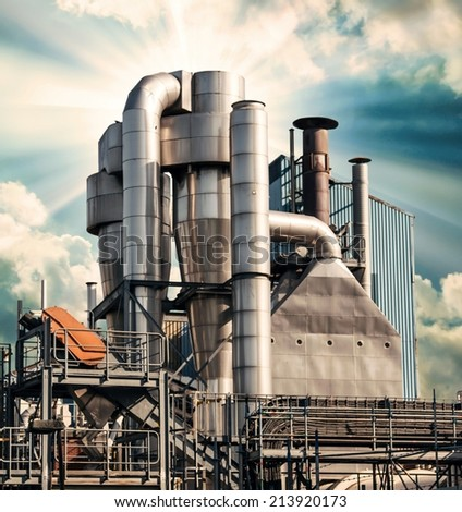An old factory, with rusty pipes and chimneys spreads risk , pointing to global warming on a hot day wide epic shot.