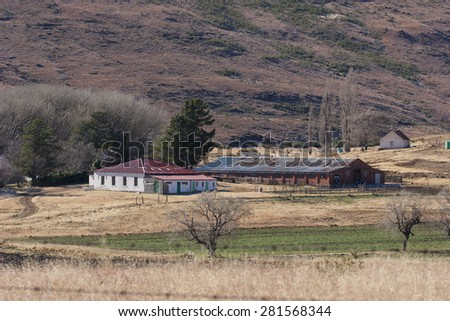 An old farmhouse sits in a valley in the South African countryside. - stock photo