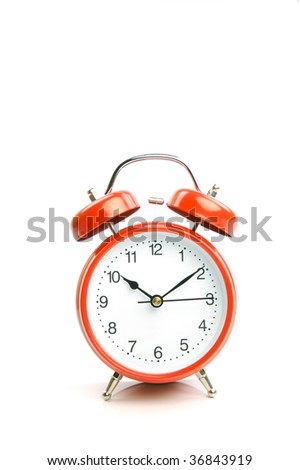 An old fashion analogue alarm clock set against a white background