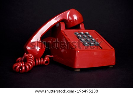 An old fashion red phone with the handset off the hook. - stock photo