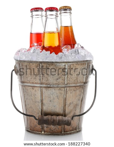 An old fashioned bucket filled with ice and soda bottles. Three different pop bottles are represented, strawberry cola and vanilla cream. Vertical format on a white background with reflection. - stock photo