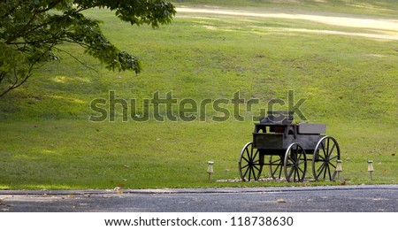 An old fashioned horse and buggy carriage on green lawn.