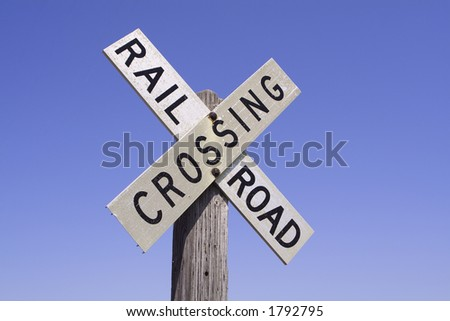 An old-fashioned railroad crossing sign with a clear deep blue sky backdrop