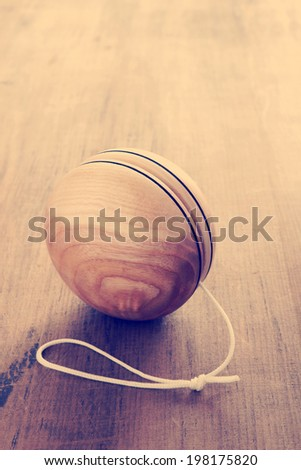 An old fashioned style wooden yoyo a retro childhood concept antique filter applied to image - stock photo