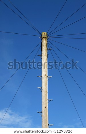 An old-fashioned telegraph pole set against a clear blue sky