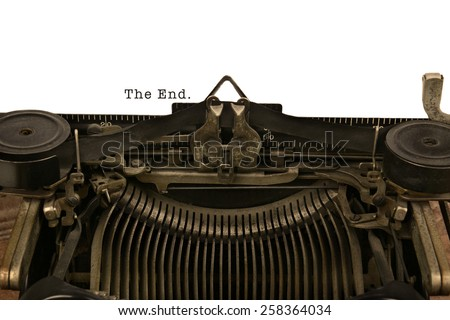 An old fashioned typewriter with the Words The End. Closeup of the antique machines ribbon and carriage. - stock photo