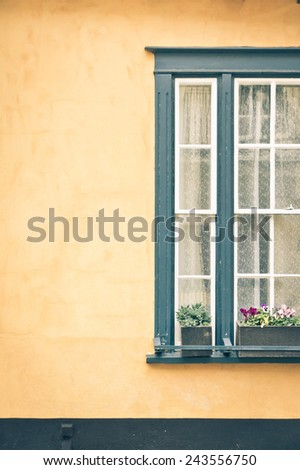An old fashioned window in a yellow wall - stock photo