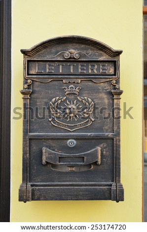 An old-fashioned wooden postbox is in the wall. - stock photo