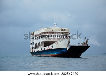 An old ferry boat on water with clouds, Zanzibar island