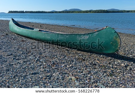 An old fiberglass green canoe resting on the pebbled shore on the coast of Maine. - stock photo