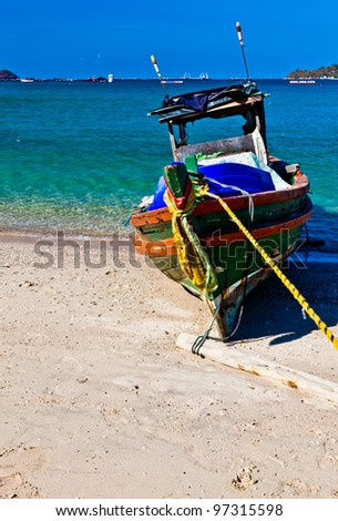 An old fishing boat on the beach in the sunshine day