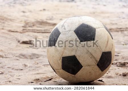 An old football or soccer ball on sand. - stock photo
