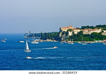 An old French fortress on an island off the coast of Cannes with pleasure boats in the blue water of the Mediterranean