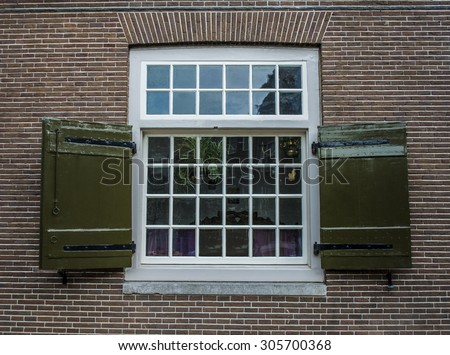An old georgian sash style window on a brick house in Amsterdam with wooden shutters - stock photo