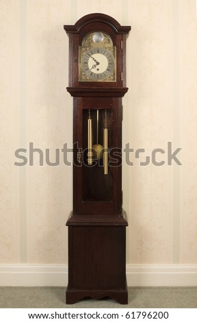 An old grand-daughter clock standing against the wall. - stock photo