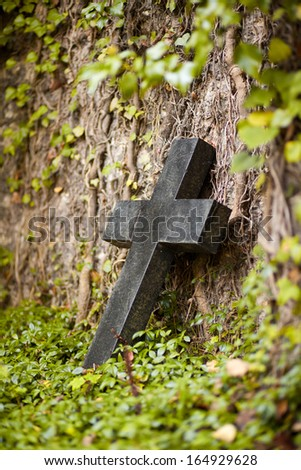 an old grave stone with a crucifix on the idyllic and historic St. John's Cemetery in Jena - stock photo