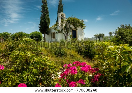 An old Greek church, drowning in greenery and flowers.