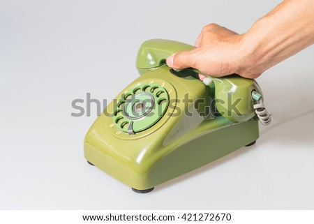 an old green rotary phone on white