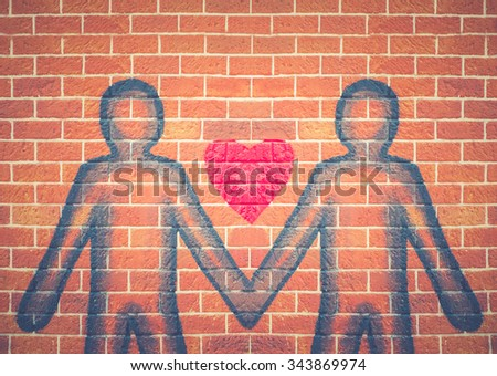 An old grunge red brick wall with red heart sprayed on a broken brick and mortar wall graffiti young people standing clasp. - stock photo