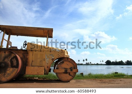 An old grungy road roller parked on the side of a lake