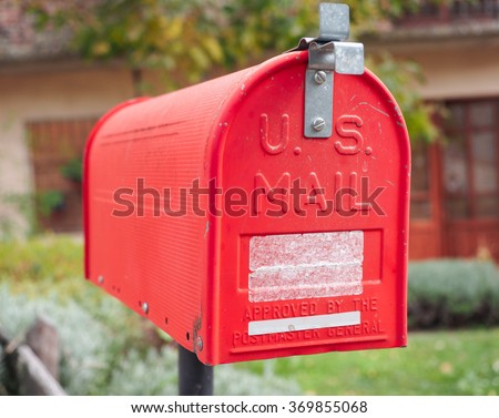 An old home letter box, red painted, with background of rural house.