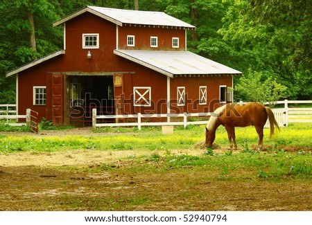 An old horse barn with a horse eating straw in the field in front of it - stock photo