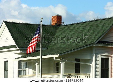 An old house with green shingled roof and an American flag - stock photo