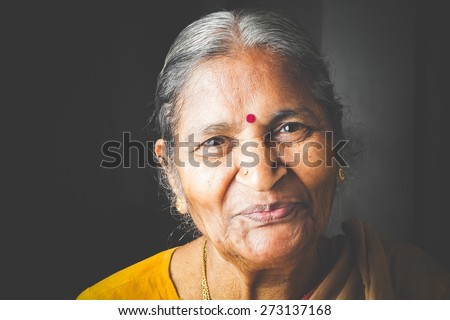 An Old Indian beautiful traditional woman smiling at he camera - stock photo