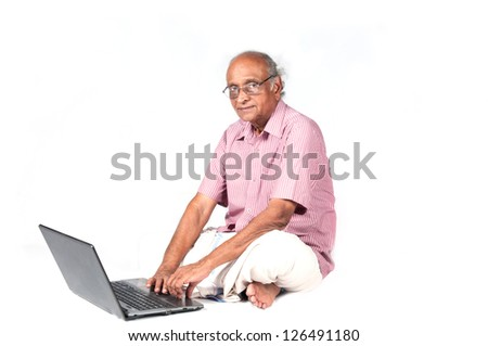 an old Indian man surfing the net after retirement - stock photo