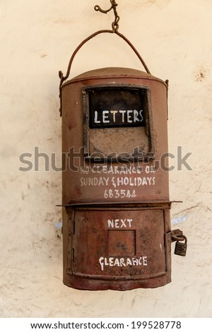 An old Indian post box hanging on a wall in Tamil Nadu. - stock photo