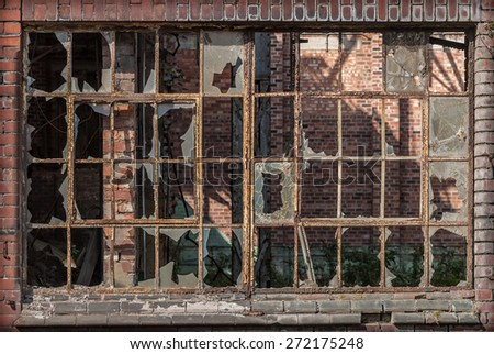 An old Industrial iron window frame rusting with broken glass. - stock photo