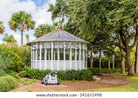 An old iron cannon by a white gazebo in a tropical park - stock photo