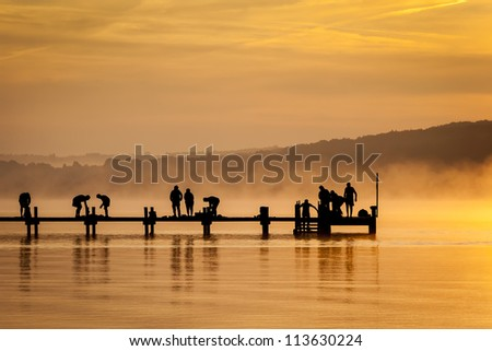An old jetty with people doing early sport - stock photo