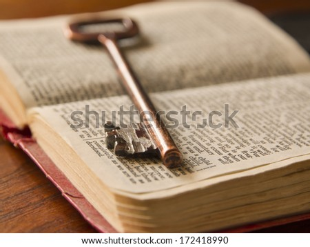 an old key on top of an old Bible - stock photo