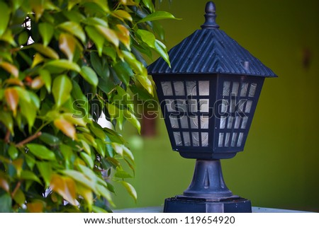 An old lamp on green wall