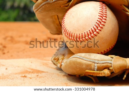 An old leather baseball mitt, or glove with a worn baseball laying on a home plate. There is clay around. Home plate needs to be dusted off. Bright sunshine, horizontal composition.