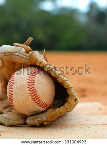An old leather baseball mitt, or glove with a worn baseball laying on a home plate. There is clay around. Home plate needs to be dusted off. Vertical composition with copy space upper right.