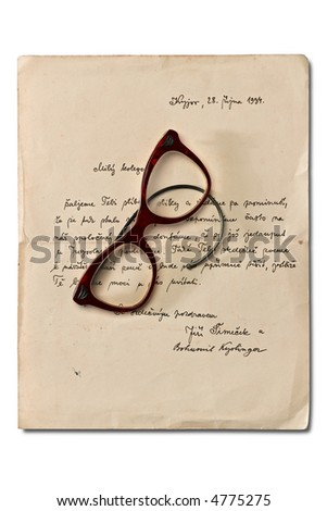 an old letter on white with broken red rim glasses
