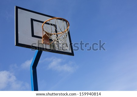 An old looking basketball hoop against a blue sky background - stock photo