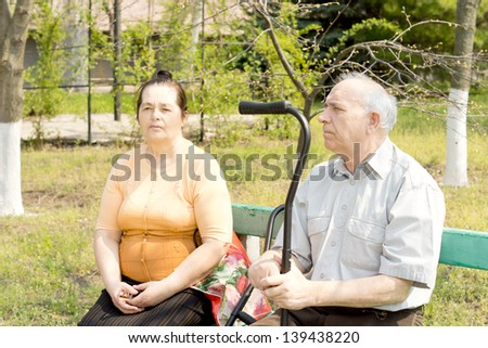 An old man and young woman sitting on the bench park - stock photo