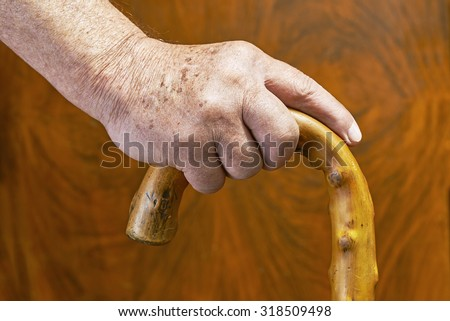 An old man holding a wooden stick
