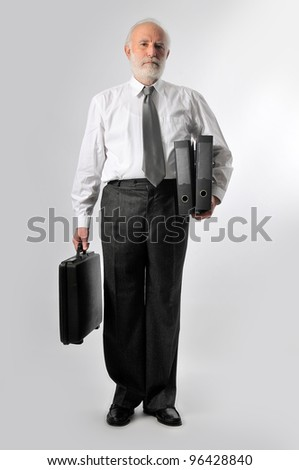 an old man holds two black folders and a suitcase - stock photo