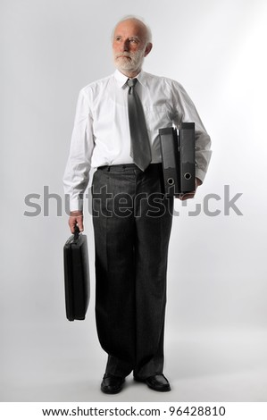 an old man holds two folders and a suitcase - stock photo