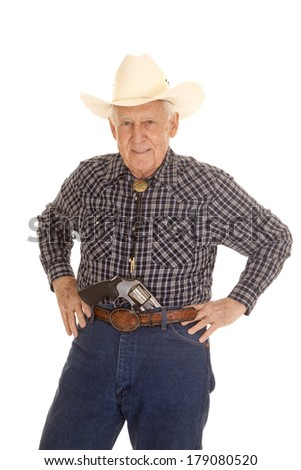 An old man in a cowboy hat with a pistol in his pants. - stock photo