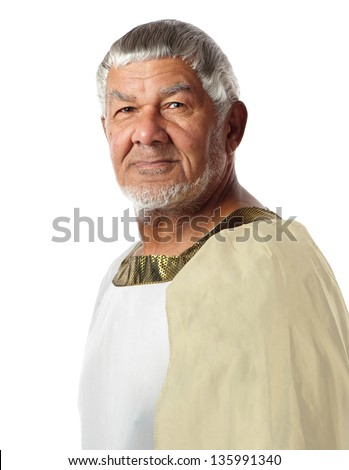 An old man in ancient garment resembles an emperor of days gone by. - stock photo