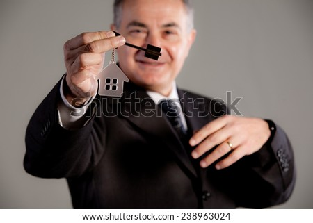 an old man reaching out a key and a little house representing real estate market affordable - stock photo